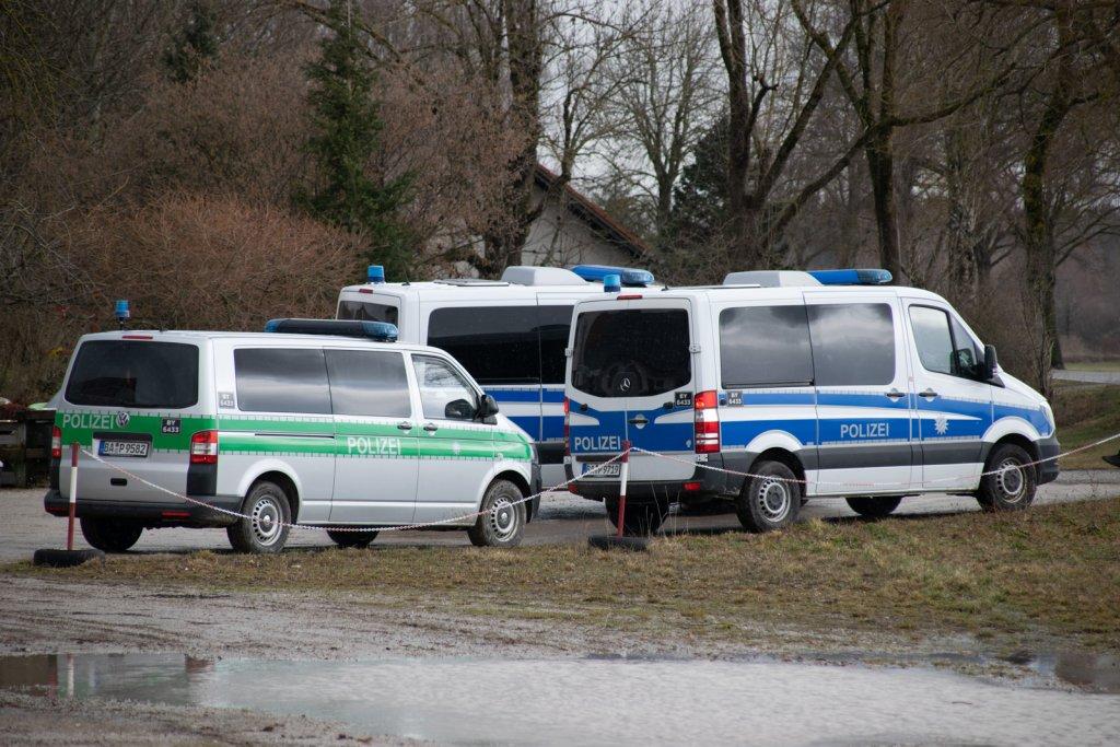 Polizeifahrzeuge hinter einer Absperrung
